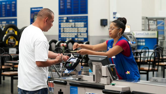 Conquisia Tyler, right, gives change to a customer at Sam's Club in Bentonville, Ark. in June.