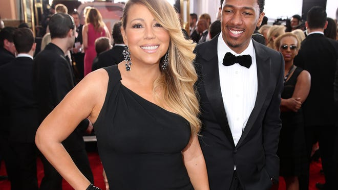FILE - This Jan. 18, 2014 file photo shows Mariah Carey, left, and Nick Cannon at the 20th annual Screen Actors Guild Awards in Los Angeles. Scholastic announced Thursday, Jan. 23, that it has acquired the coupleís ìRoc and Roeís Twelve Days of Christmas,î a picture story scheduled for release this fall. Illustrated by A.G. Ford, the book is a holiday tale featuring twins Moroccan and Monroe, whom Carey gave birth to in 2011. (Photo by Matt Sayles/Invision/AP, File) ORG XMIT: NYET410