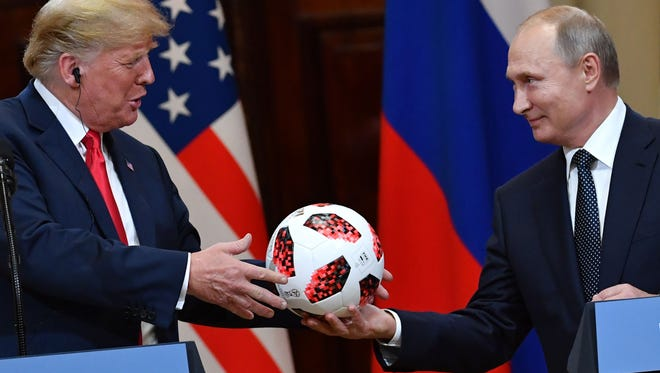 TOPSHOT - Russia's President Vladimir Putin (R) offers a ball of the 2018 football World Cup to US President Donald Trump during a joint press conference after a meeting at the Presidential Palace in Helsinki, on July 16, 2018.