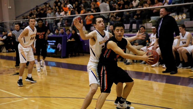 Kirtland Central's Jaben Haws, No. 22 in white, defends Gallup's Johnny Blueeyes, No. 34 in black, during Friday's District 1-5A game at Bronco Arena. Both teams will square off against in Monday's district championship tiebreaker game at Shiprock.