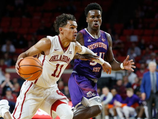 Oklahoma guard Trae Young (11) drives past Northwestern State forward Brandon Hutton, right, in the second half of an NCAA college basketball game in Norman, Okla., Tuesday, Dec. 19, 2017. Oklahoma won 105-68. (AP Photo/Sue Ogrocki)
