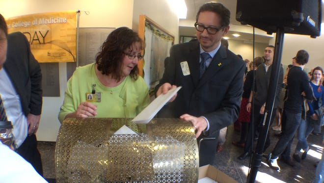 University of Iowa Carver College of Medicine registrars Annette Griffin, left, and Damien Ihrig, right, insert letters that would reveal where 76 students would go for their residencies Friday morning at the college's Match Day ceremony.