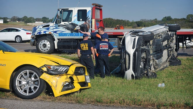 Emergency crews work the scene of a two-vehicle collision Thursday morning on I-44 in Burkburnett. The driver of the white was ejected in the rollover accident and was taken to the hospital with serious injuries.