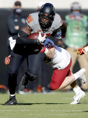 Oklahoma State's Jelani Woods is tackled by Iowa State's Mike Rose during the Cowboys' 24-21 win Saturday. Woods had three catches for 54 yards, including a 34-yard touchdown.