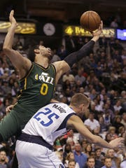 Utah Jazz center Enes Kanter (0) is fouled by Dallas Mavericks forward Chandler Parsons (25) during the first half of an NBA basketball game Wednesday, Feb. 11, 2015, in Dallas.