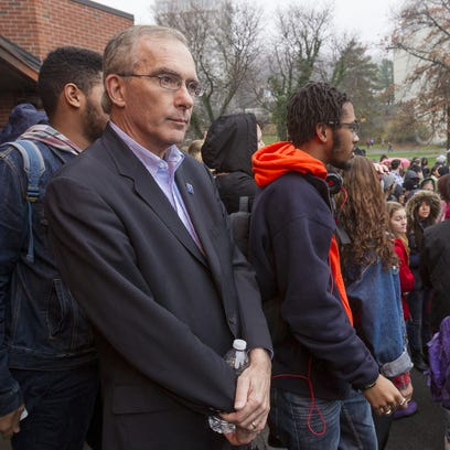 Ithaca College President Tom Rochon watches protesters