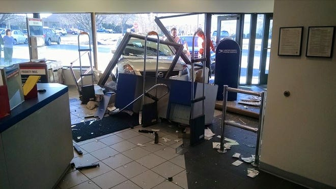 A Washington Township woman's Nissan smashed through a U.S. Postal Service storefront in the township.