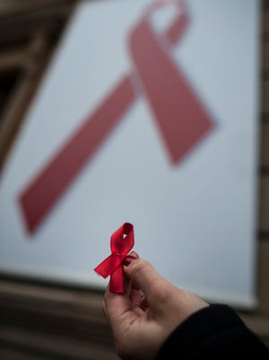 A woman holds a red ribbon, the symbol of the fight against AIDS, during a demonstration on World AIDS Day, in Pamplona, Spain.