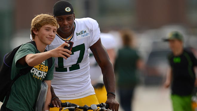 Green Bay Packers receiver Davante Adams (17) takes a selfie with a fan before training camp practice at Ray Nitschke Field.