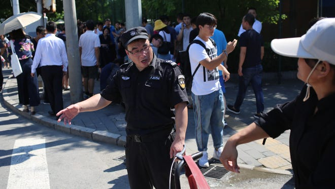 Chinese policeman stand guard outside the U.S. embassy after a blast near the US embassy area in Beijing, China, July 26, 2018.