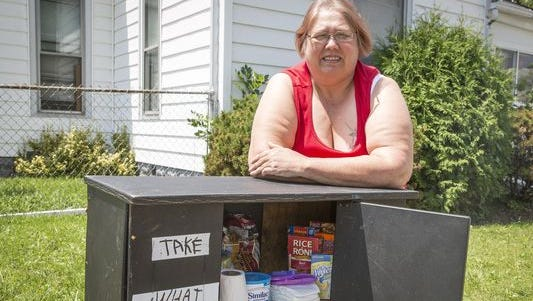 Jeannetta Presley stands with her blessing box on Wednesday at at the corner of East Eighth and South Monroe streets in Muncie. The box is stocked with non-perishable food items and basic toiletries for those in need.