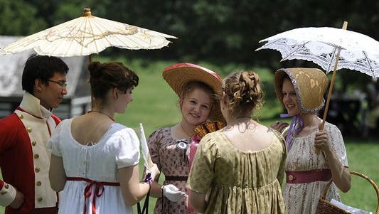 Participants dressed in regency attire gather to chat at the Sixth Annual Jane Austen Festival at Locust Grove.