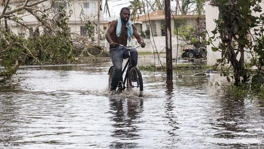 A man rides a bike through high water in Loiza, Puerto Rico, on September 22, 2017. Many on the island have lost power, running water, and cell phone service after Hurricane Maria.