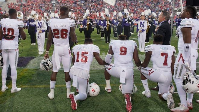 Nebraska linebacker Michael Rose-Ivey (15), defensive end DaiShon Neal (9) and linebacker Mohamed Barry (7) kneel during the national anthem before the team's NCAA college football game against Northwestern in Evanston, Ill., on Saturday, Sept. 24, 2016.