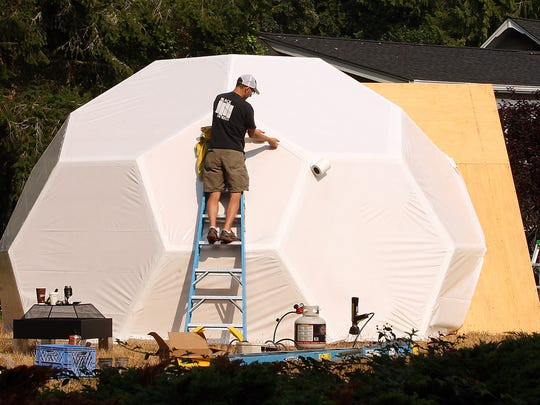 Mead Trick, of Blackmouth Design, works on the plastic shrink-wrap exterior of their geodesic dome on Bainbridge Island on Friday, August 11, 2017.