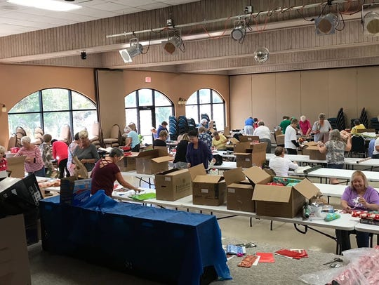 Members of North Fort Myers' Del Tura Golf & Country Club wrap presents for the needy as part of the Nations Association Charities.