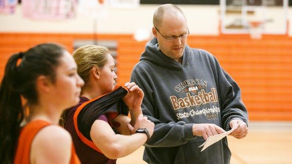 Coach Casey Williams talks to players at a practice for the Sprague High School girl's basketball team on Thursday, Jan. 12, 2017.