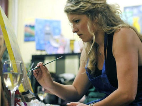 "Painter Sara Netherland focuses on the canvas during an art class class a Pinot's Palette in Colorado in 2013. The national chain of paint-and-sip art studios, whose motto is ""paint, drink, have fun,"" will open its first Somerset County location on Friday in Somerville."