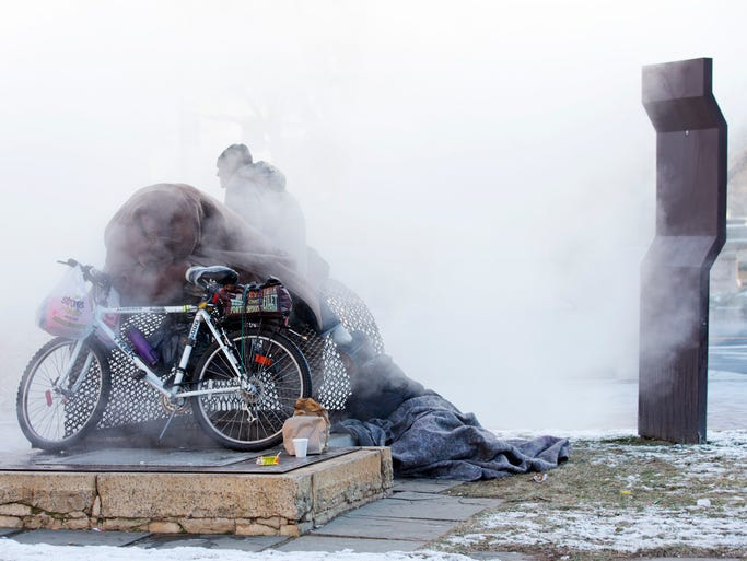 Nicholas Simmons, 20, of Greece, left,   warms himself on a steam grate with three men by the Federal Trade Commission, just blocks from the Capitol, during frigid temperatures in Washington D.C. on Jan. 4.