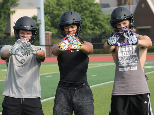 Showing off the receiving gloves for CHCA are (from left) running backs DJ Ames and Alex Bernard and receiver Julian Herman