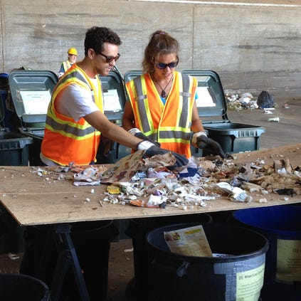 Arizona State University graduate students Andy Stein (left) and Cassie Lubenow sort through refuse as part of a trash study meant to increase recycling in Phoenix.