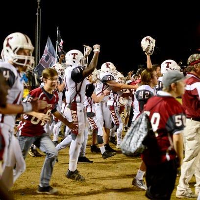 Tate High School players celebrate a close victory,