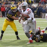 Ohio State quarterback J.T. Barrett (16) breaks away from Michigan linebacker James Ross for a touchdown during the second half of an NCAA college football game, Saturday, Nov. 28, 2015, in Ann Arbor, Mich.