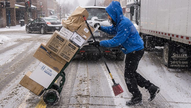 """Kalvin Watson, a truck driver for Bell and Sons, delivers restaurant and bar supplies in downtown Northville. There are few snow days in this business. Watson said, """"I'm kind of proud of all the drivers on the road."""" noting that he sees people driving carefully and at lower speeds on this sloppy day."""