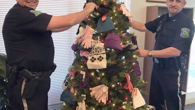 Helping decorate the tree with items collected so far are LOPD Officers Kelly Lowe (left) and Mark Kordula.
