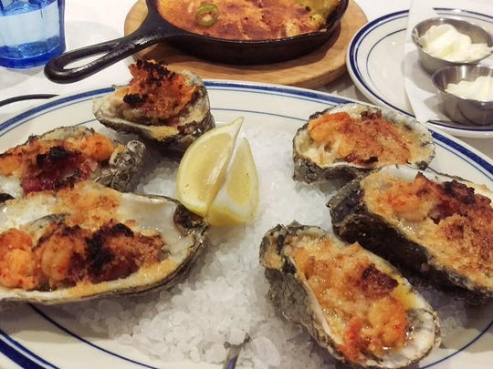 """""""Brunch oyster"""" topped with citrus butter, bacon and quail egg, is a brunch favorite at Saltine."""