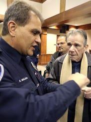 Officer Kevin Mullikin (left) describes how he pried