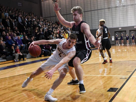 Waukee's Dylan Jones (4) tries to work to the basket as Dowling's John Waggoner (33) defends during a basketball game between the Waukee Warriors and the Dowling Maroons on Tuesday, Jan. 30, 2018, at Waukee High School.
