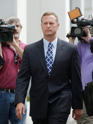 Lt. Col. Jeffrey Krusinski, who led the Air Force's Sexual Assault Prevention and Response unit, is surrounded by members of the media while leaving the Arlington County General District Court, Thursday, July 18, 2013 in Arlington, Va.