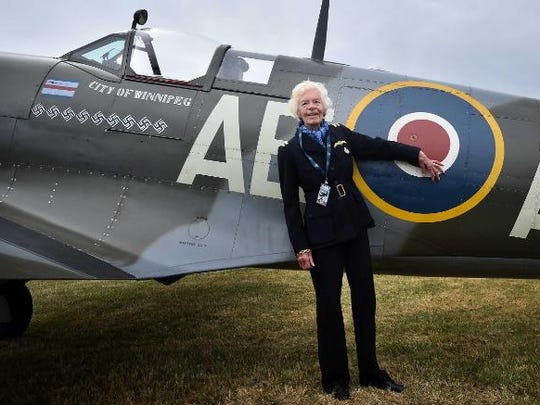 Mary Ellis stands next to a Spitfire fighter at Biggin