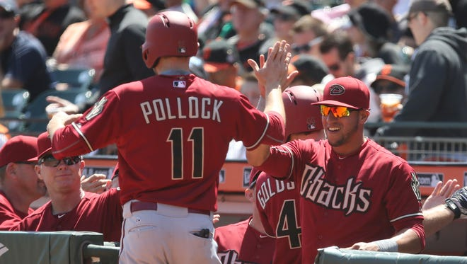 Apr 19, 2015: Arizona Diamondbacks center fielder A.J. Pollock (11) high fives left fielder David Peralta (6) after scoring on a two run home run by first baseman Paul Goldschmidt (not pictured) against the San Francisco Giants during the first inning at AT&T Park.