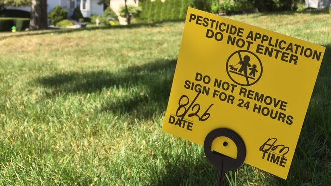 A pesticide warning sign on a residential lawn in White Plains.