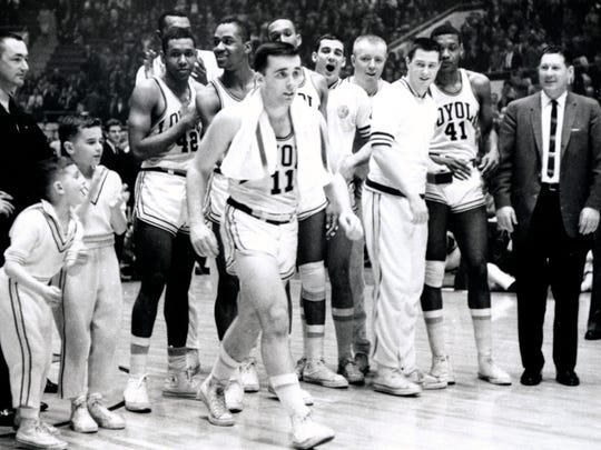With his teammates, including Racine's Chuck Wood, cheering on, Loyola's John Egan walks to receive his award after the Ramblers beat Cincinnati  for the 1963 NCAA championship.