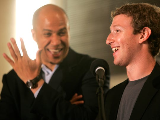 Newark Mayor Cory Booker, left, laughs as Mark Zuckerberg,
