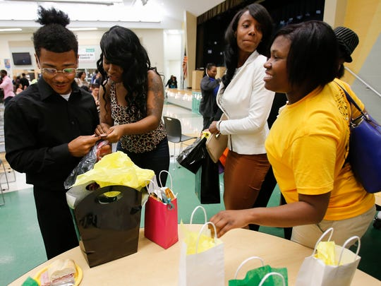 Taft High School graduating senior Rico Sanford, 18, far left, who will be attending the University of Cincinnati in the fall, pumps his first with excitement after receiving UC gear from English teacher Sinita Scott as a graduation present, Thursday, May 12, 2016, at Taft High School in the West End.