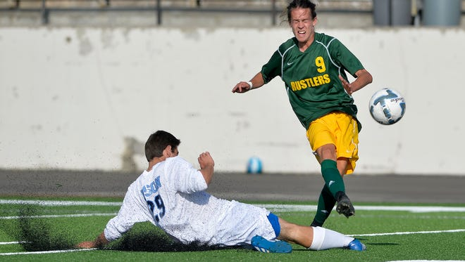 Great Falls High's Max Rubino attempts a sliding tackle on CMR's Braden Stremcha during the crosstown soccer match, Tuesday at Memorial Stadium.