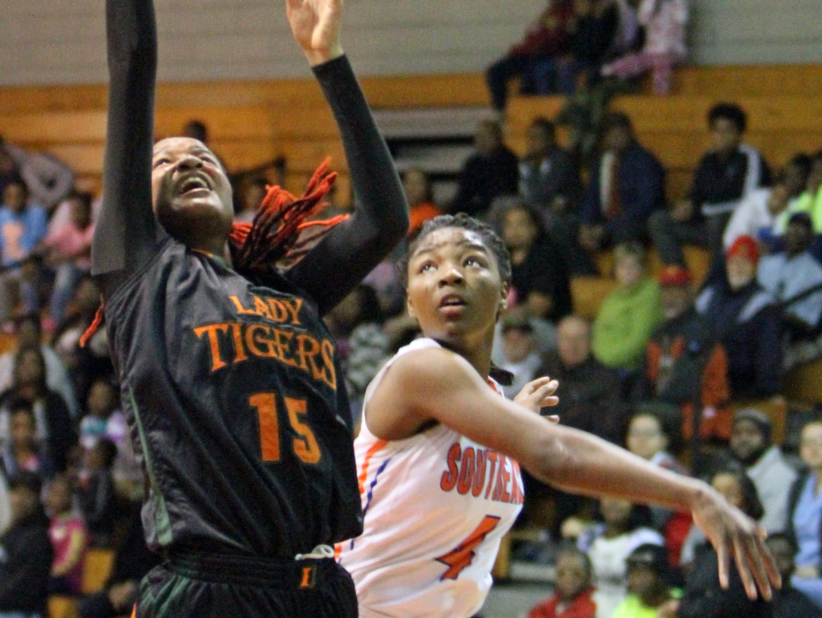 Dunbar's Dekeriya Patterson drives past Southeast's Shauntavia Green to the basket in the Class 5A-Region 3 semifinals Tuesday night at Buzz Narbut Gymnasium.
