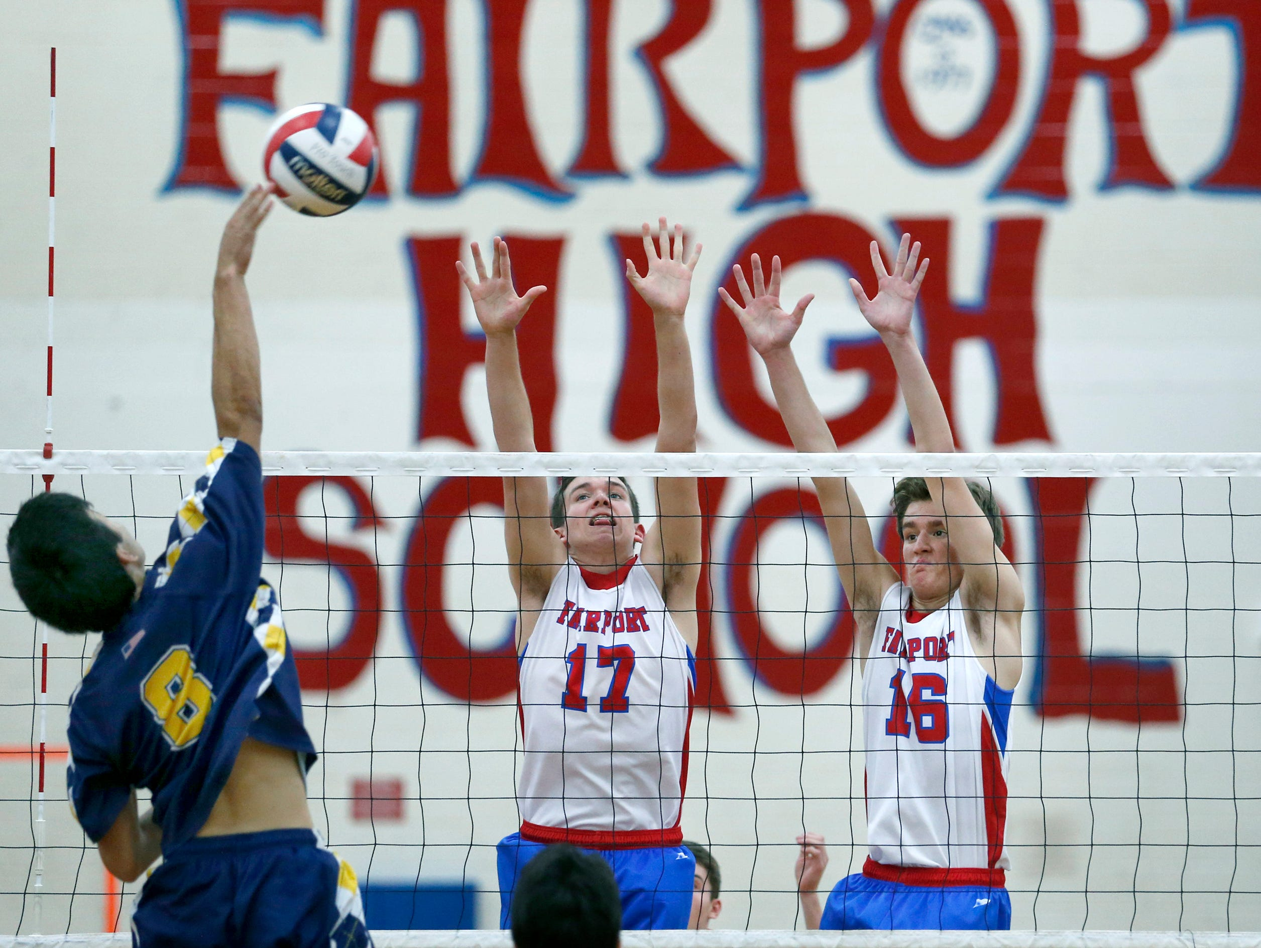 Victor's Kyle Sumarsono attacks as Fairport's Jack Scheutzow and Mitch D'Agostino get ready to block in the first set at Fairport High School.