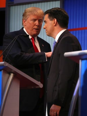 President-elect Donald Trump talks with Wisconsin Gov. Scott Walker during the GOP presidential debate in August 2015 in Cleveland. Walker is banking on President-elect Trump to give states more leeway to design their own social, education and economic programs without too many federal strings