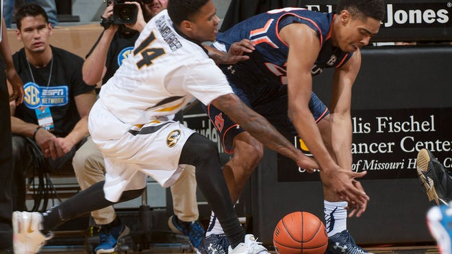 Auburn's TJ Lang, right, and Missouri's Keith Shamburger, left, vie for a loose ball during the first half of an NCAA college basketball game Tuesday, March 3, 2015, in Columbia, Mo. (AP Photo/L.G. Patterson)