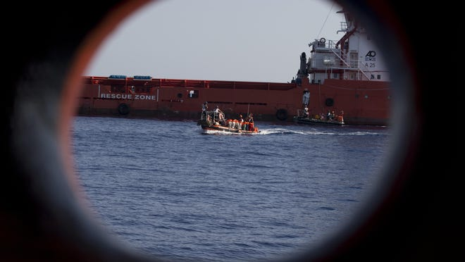 In this Wednesday, Aug. 30, 2017 file photo, rescuers transfer migrants rescued by an oil rig supply ship to the Aquarius vessel of SOS Mediterranee and MSF (Doctors Without Borders) NGOs, in the Mediterranean Sea, north of Libyan coast.