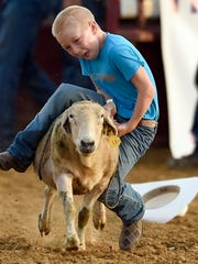 JASON CLARK / THE GLEANER Rowdy Hibbs, 9, of Clay hangs on for as long as he can after losing his hat while competing in the Mutton Bustin! competition at the start of the rodeo during the Henderson County Fair at the fairgrounds in Henderson in July.  This year was the first time in 27 years the rodeo was featured during the fair.