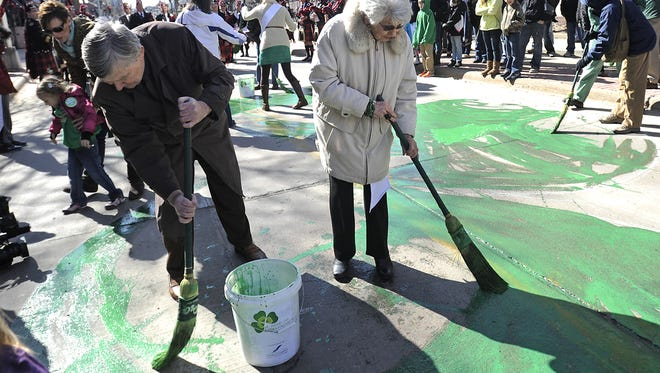 Evan Nolte and Sylvia Henkin paint the shamrock at Ninth Street and Phillips Avenue before the 34th Annual St. Patrick's Day Parade on March 16, 2013.