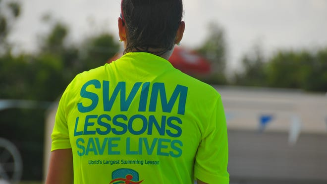 "Swim instructor Seth Badana was giving four young students advanced beginner swim lessons early Wednesday morning at the Cocoa Beach Aquatic Center. Another instructor nearby  teaching classes wears the appropriate shirt with ""Swim Lessons Save Lives"" on the back."