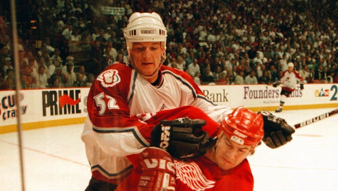 Detroit's Keith Primeau gets pinned on the boards by Colorado's Adam Foote as they both go after the puck in the second period during a game in 1996.