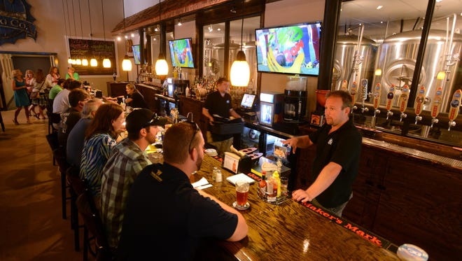 Ocean City Brewing Company owner Joshua Shores, right, talks with customers during the brewpub's grand opening. Shores has admitted guilt in connection with a $2.5 million fraud scheme.
